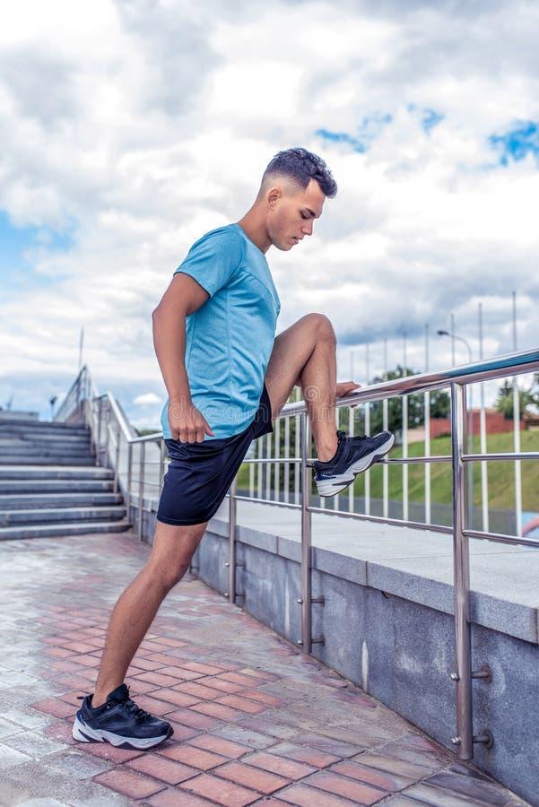 Formation masculine de jambe d'athlète s'étendant réchauffant des muscles des jambes, dans la ville d'été, étirant des muscles av images libres de droits