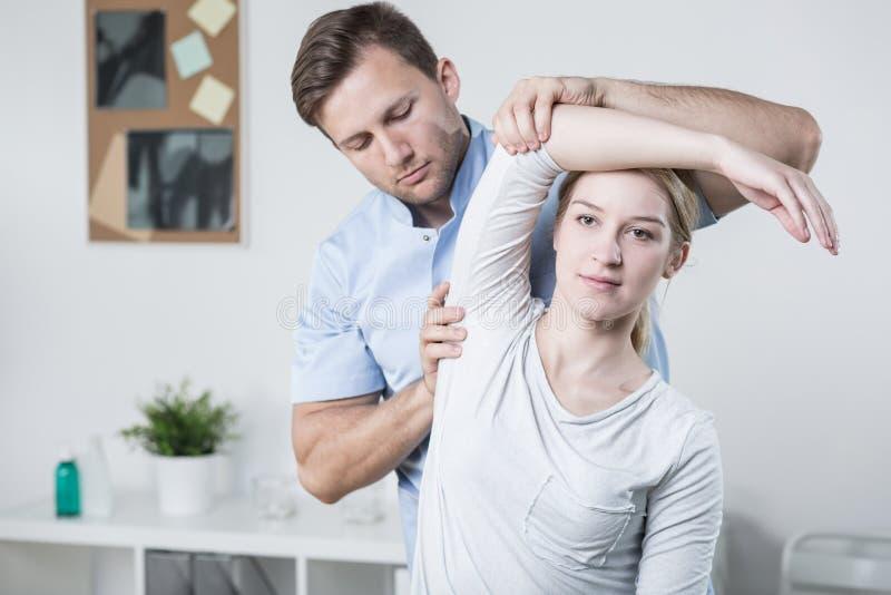 Formation masculine de physiothérapeute avec le patient image stock