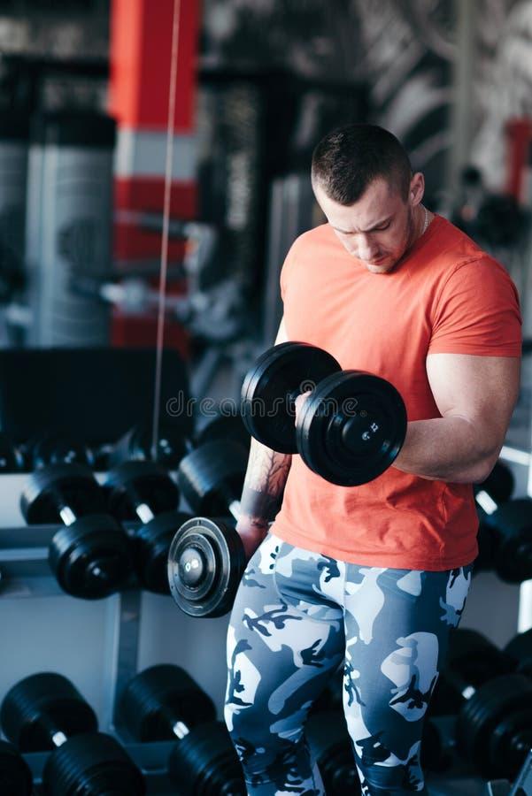 Formation musculaire d'homme avec l'haltère noire dans le gymnase photos stock
