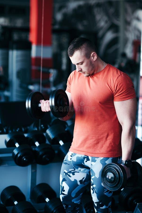 Formation musculaire d'homme avec l'haltère noire dans le gymnase photo libre de droits