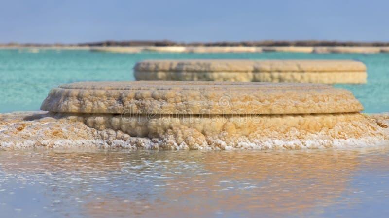Formations de sel dans le plan rapproché des eaux de bleu et de turquoise de mer morte photographie stock