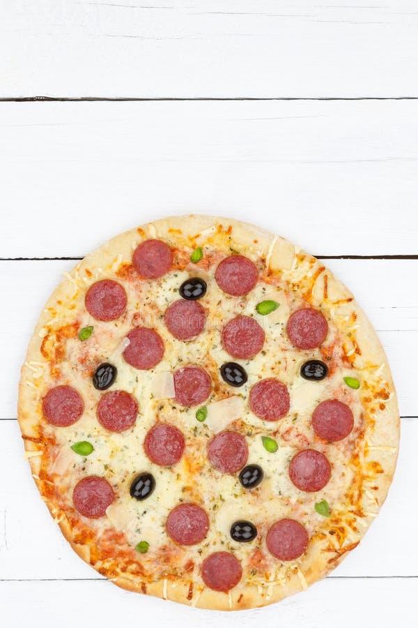 Formato de retrato del espacio de la copia del copyspace del salami de los salchichones de la pizza desde arriba en el tablero de fotografía de archivo