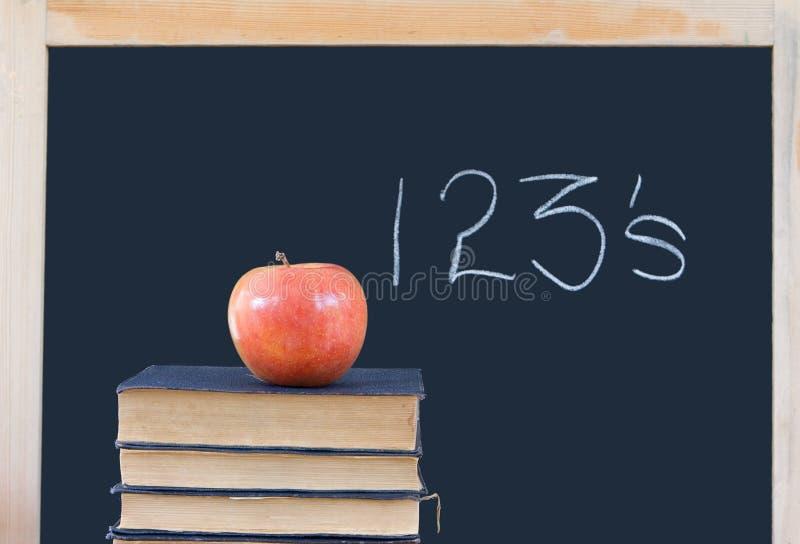 Formazione: 123's sulla lavagna, libri, mela fotografie stock libere da diritti