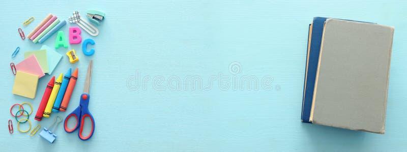 Formazione e di nuovo al concetto del banco cancelleria sopra fondo blu di legno Vista superiore, disposizione piana fotografia stock libera da diritti