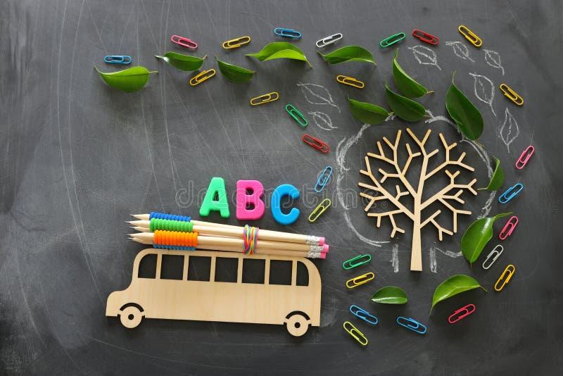 Formazione e di nuovo al concetto del banco Foto di vista superiore del bus e delle lettere di legno di ABC, matite sul tetto acc fotografie stock libere da diritti