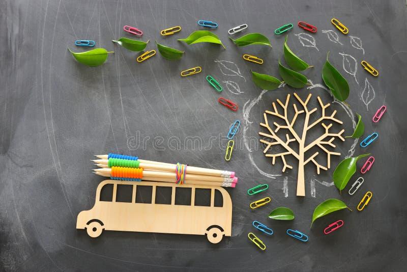 Formazione e di nuovo al concetto del banco La foto di vista superiore del bus e delle matite di legno sul tetto accanto all'albe fotografie stock