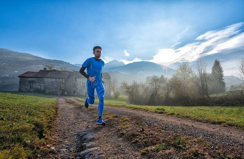 Formazione professionale dell'atleta del corridore su una sporcizia della montagna immagini stock libere da diritti