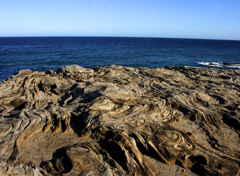 Formazione rocciosa davanti all'oceano immagini stock