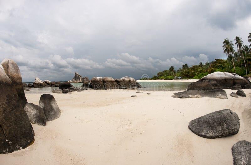 Formazione rocciosa naturale in mare e sulla spiaggia di sabbia bianca con le palme nell'isola del Belitung, Indonesia fotografia stock