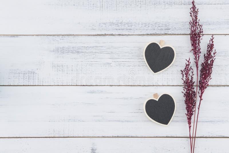 Formbrädet för två hjärta dekorerar med violeten torkade blomman arkivbilder