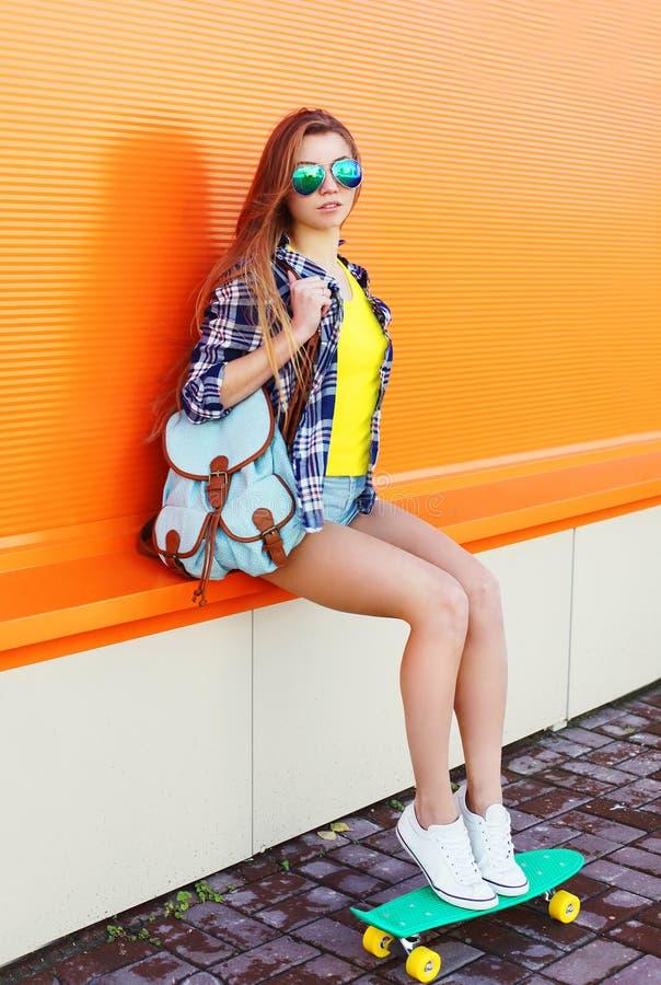 Forme óculos de sol vestindo da menina consideravelmente fresca com skate imagens de stock royalty free
