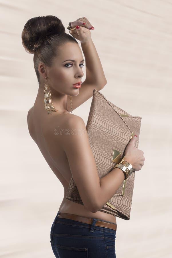 Forme al brunette en vaqueros con el bolso grande dado vuelta de tres cuartos imágenes de archivo libres de regalías