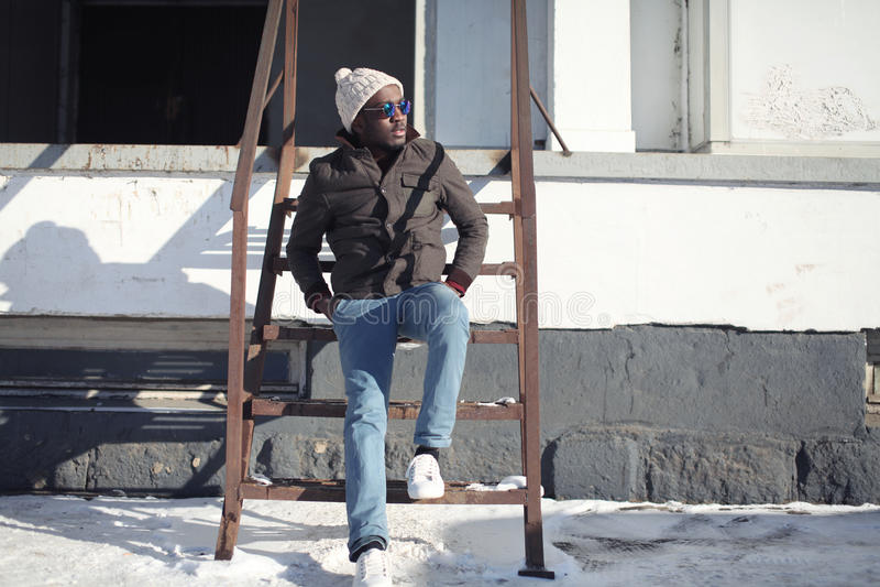 Forme al hombre africano joven elegante que lleva un sombrero de la chaqueta sobre estilo urbano de la calle del invierno del fon fotos de archivo libres de regalías