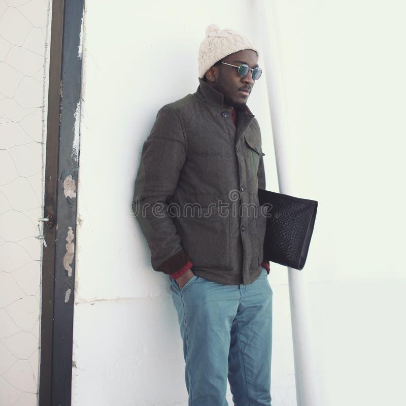 Forme al hombre africano joven elegante que lleva una chaqueta con el sombrero y el bolso imagen de archivo