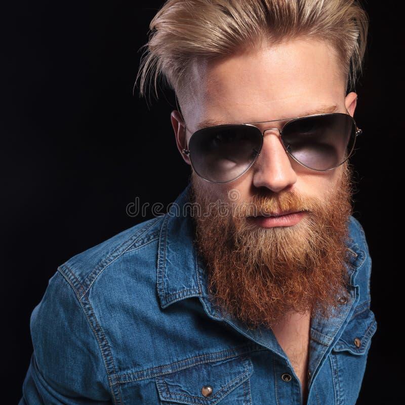 Forme al hombre en la presentación de las gafas de sol de la camisa que lleva azul imagenes de archivo