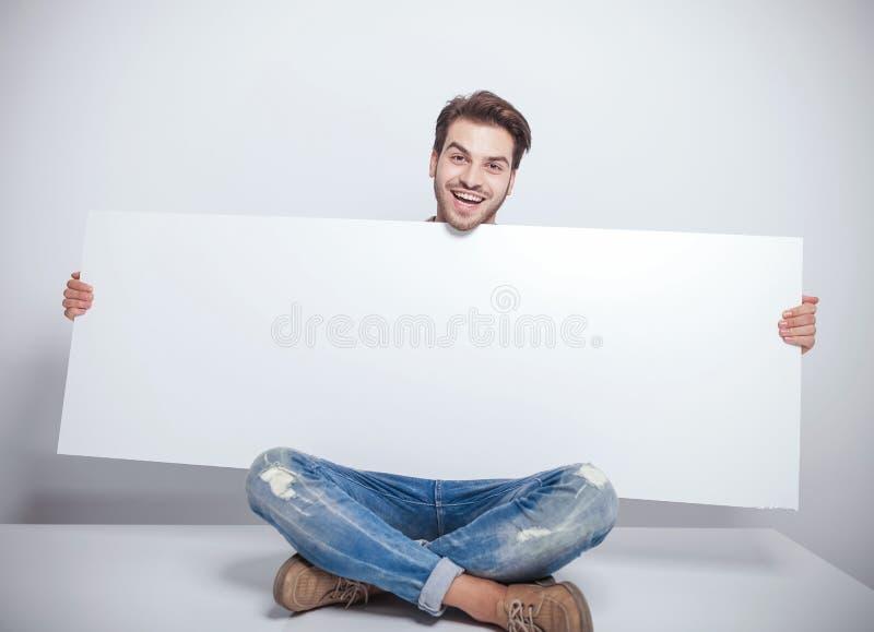 Forme al hombre que lleva a cabo a un tablero vacío grande mientras que se sienta imagen de archivo