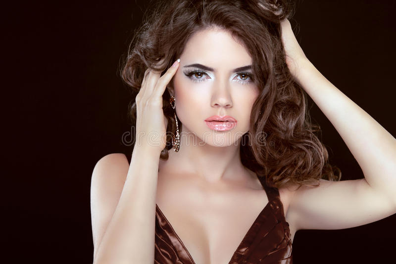 Forme a beleza o modelo moreno da jovem mulher com cabelo ondulado e valor máximo de concentração no trabalho imagem de stock