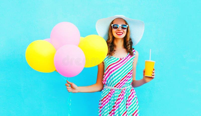 Forme a controles bastante sonrientes de la mujer a la taza del zumo de fruta con los globos coloridos de un aire fotos de archivo