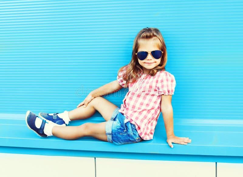 Forme a criança da menina que levanta no fundo azul colorido imagens de stock