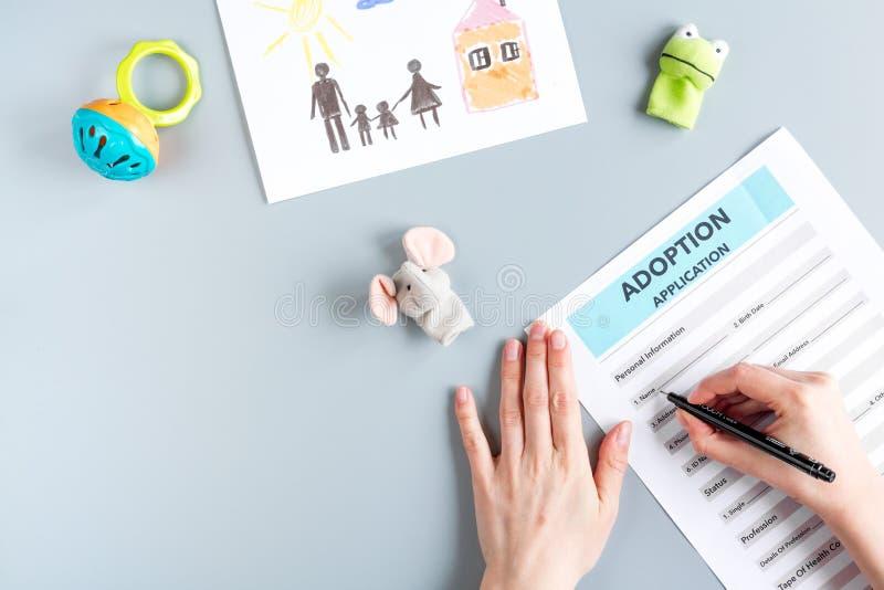 Forme d'adoption dans le concept de la famille sur la maquette grise de vue supérieure de fond photos stock