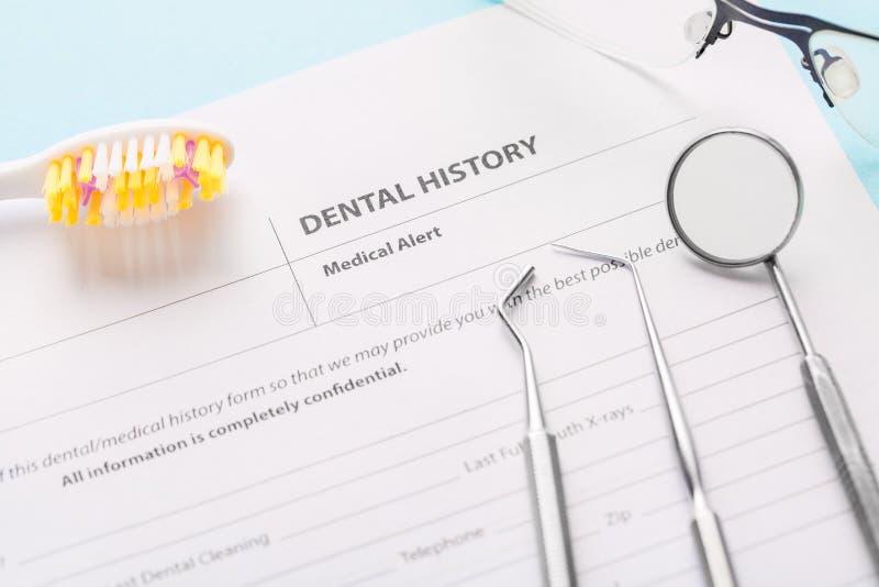 Forme d'histoire dentaire avec les instruments dentaires en acier professionnels, le miroir près de la brosse à dents et les verr images libres de droits