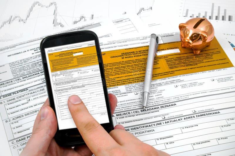 Forme d'impôt sur le revenu de poli de remplissage d'homme sur le mobile photographie stock