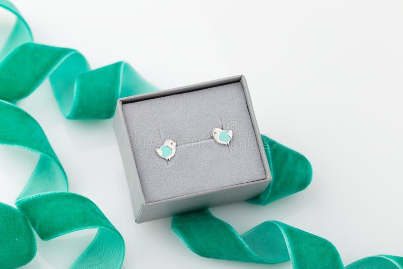 Forme d'oiseau avec les goujons en bon état de boucle d'oreille de coeur dans le boîte-cadeau gris sur le whi photographie stock