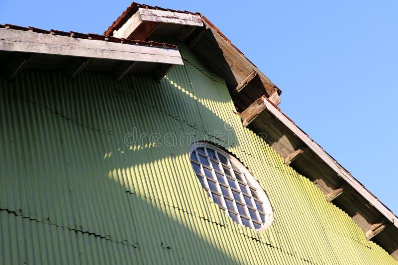 Forme de cercle de maison de rayon du soleil sur le mur et le toit verts de zinc photos libres de droits