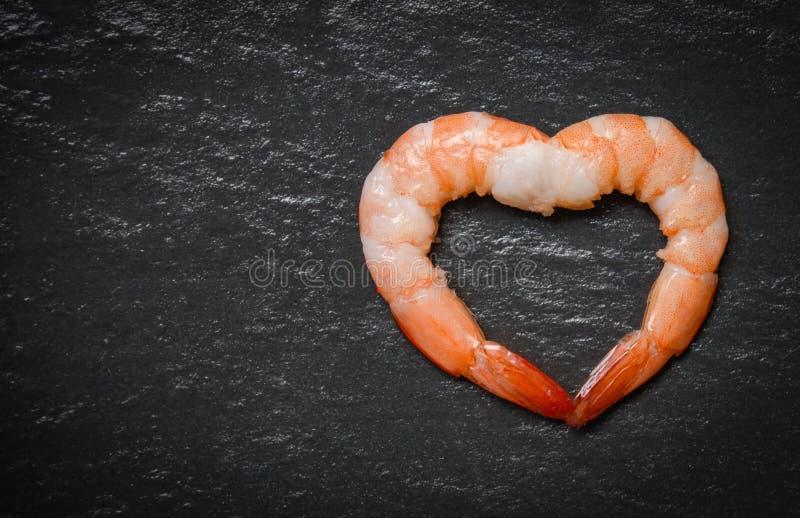 Forme de coeur de crevettes des fruits de mer deux/crevettes roses cuites de crevette sur le fond foncé photographie stock