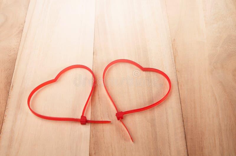 Forme de coeur de serres-câble sur le fond en bois, CCB abstrait de vacances images stock