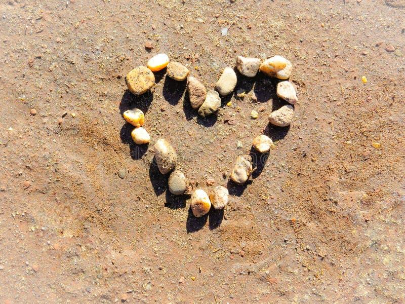 Forme de coeur faite à partir des cailloux de roche dans le sable image libre de droits