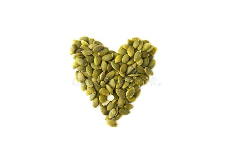 Forme de coeur de graines de citrouille, sur un fond blanc, d'isolement Casse-croûte végétarien sain Nourriture végétarienne d'am photo stock