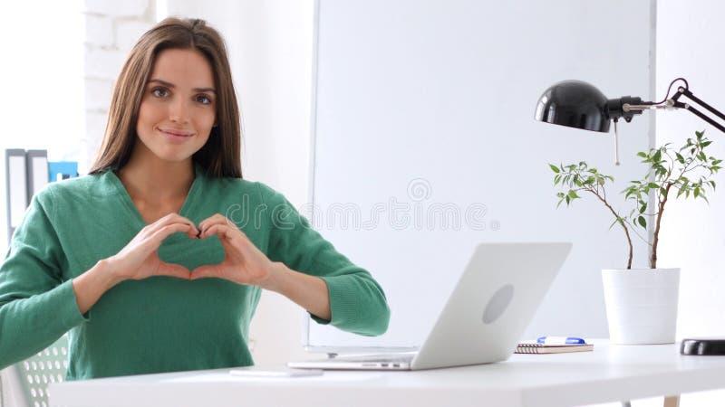 Forme de coeur par la femme, fond blanc photos stock
