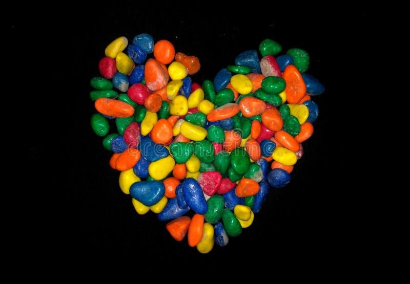 Forme de coeur sur le fond noir, forme de coeur faite de caillou coloré image libre de droits
