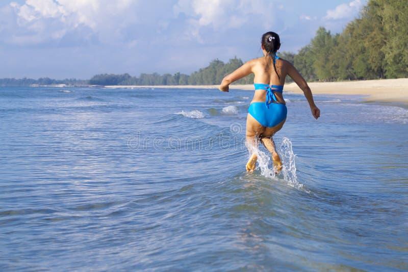 Forme de femme grande et saut bleu de bikini sur la vague à la plage photographie stock
