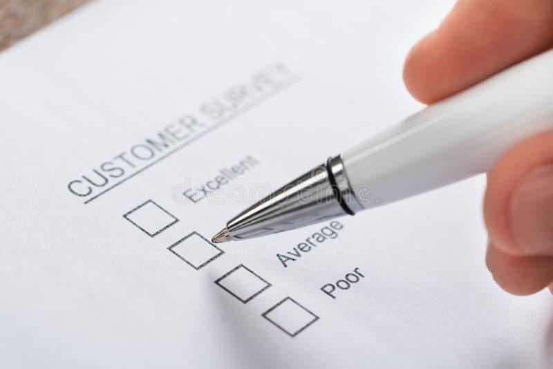 Forme de Person Hands Filling Customer Survey photographie stock libre de droits