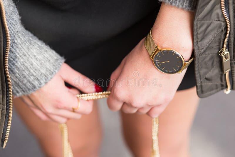 Forme detalhes, mulher de negócio nova que guarda seu saco joia dourada vestindo, e relógio classificado em cores mornas fotografia de stock