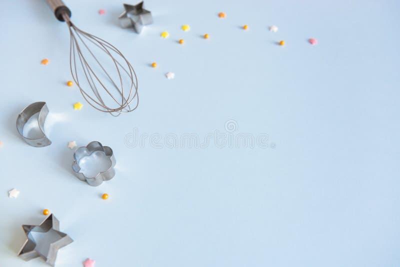 Forme differenti delle taglierine metalliche del biscotto e sbattere su fondo blu Concetto del confettiere e del forno Copi lo sp immagini stock