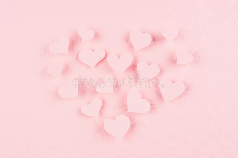 Forme el corazón de los corazones de papel rosados del vuelo en fondo rosado suave del color Diseño del día de tarjetas del día d fotos de archivo libres de regalías