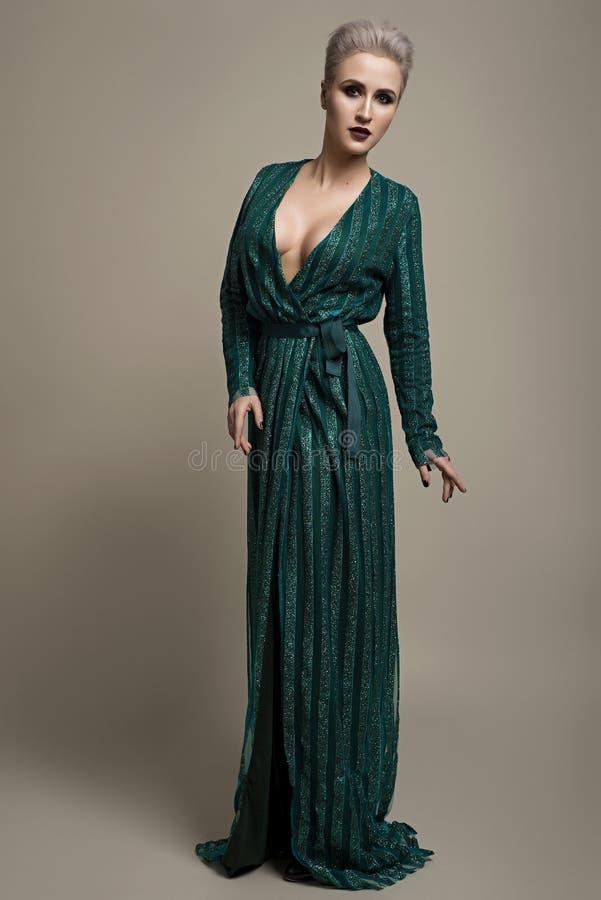 Forme el estudio tirado de mujer hermosa con el vestido de noche del maquillaje que lleva y del peinado foto de archivo