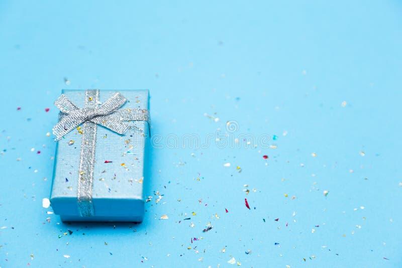 Forme el fondo azul con la opinión del regalo o de la caja de regalo, del corazón y de top de las lentejuelas fotografía de archivo
