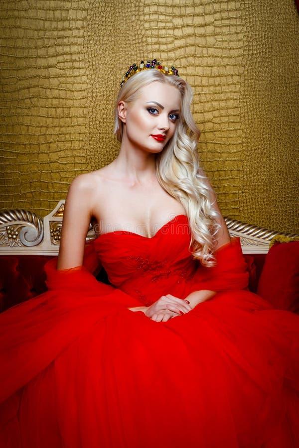 Forme el lanzamiento de la mujer rubia hermosa en un vestido negro largo que se sienta en el sofá fotos de archivo libres de regalías