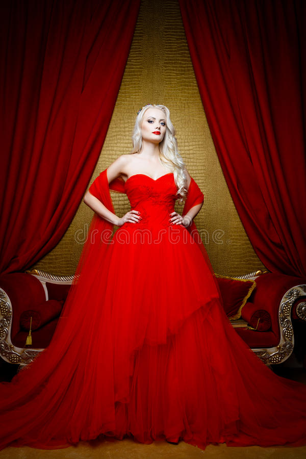 Forme el lanzamiento de la mujer rubia hermosa en un vestido rojo largo imagen de archivo