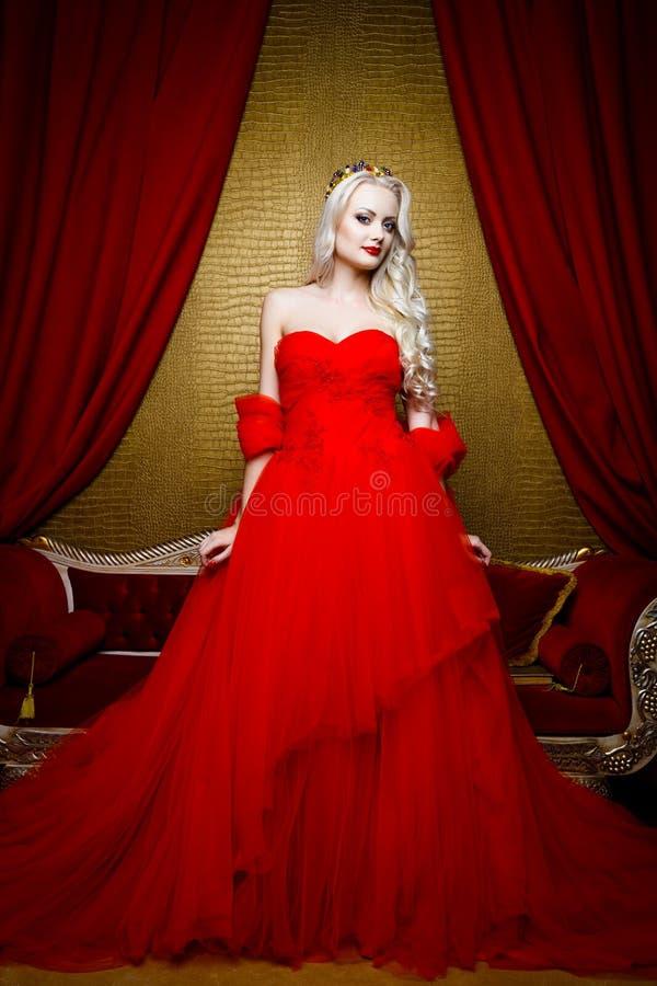 Forme el lanzamiento de la mujer rubia hermosa en un vestido rojo largo que se sienta en el sof fotografía de archivo libre de regalías