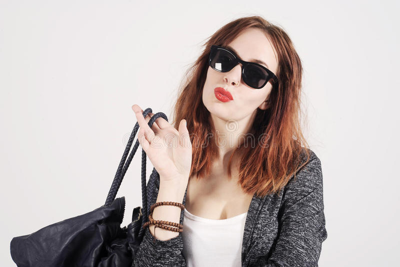 Forme el modelo de moda joven en la ropa agradable que presenta en el estudio Gafas de sol y bolso que llevan fotografía de archivo libre de regalías