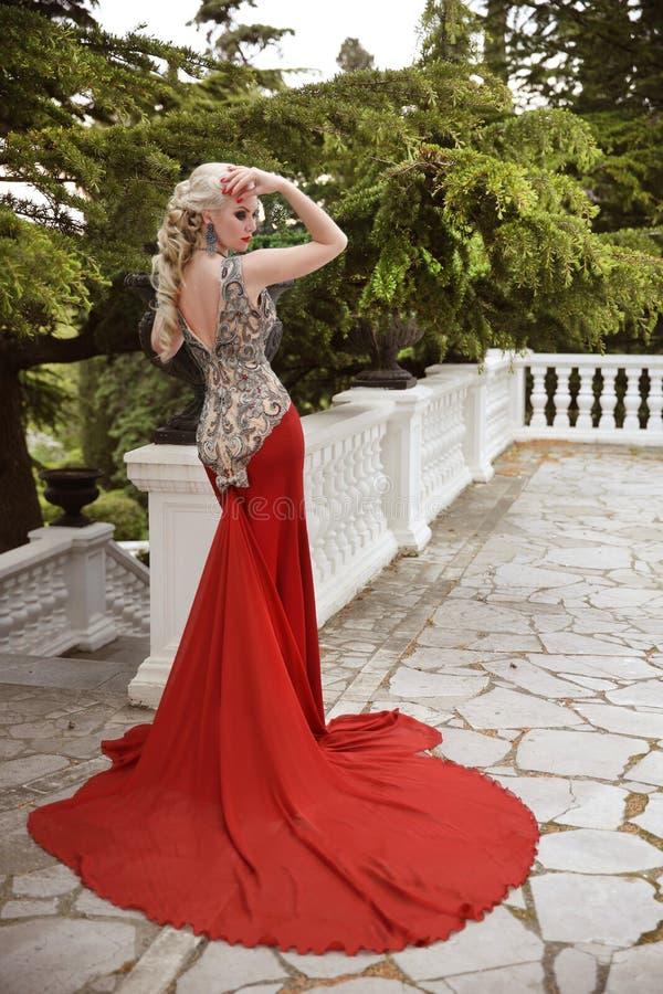 Forme el modelo rubio elegante de la mujer en vestido rojo con el tren largo de imagen de archivo