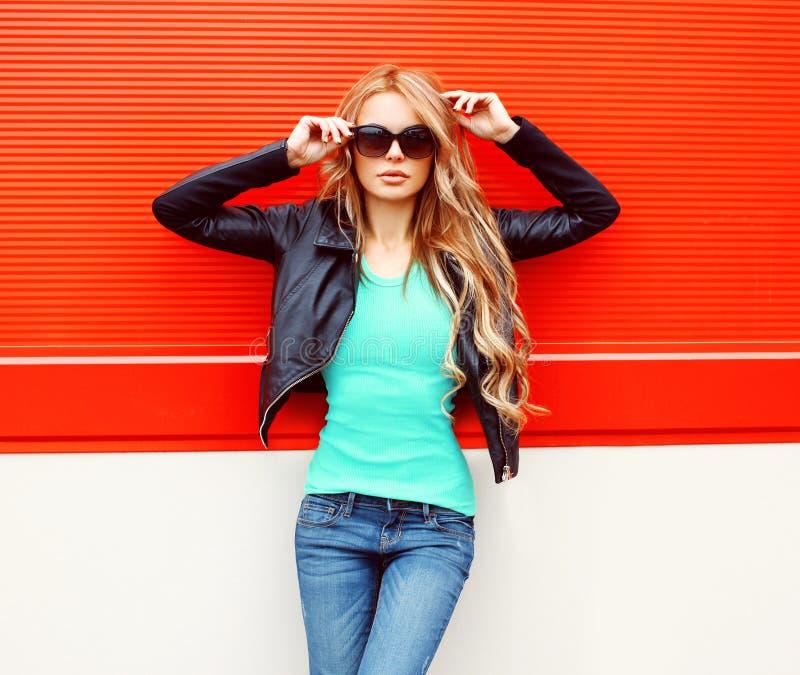 Forme el modelo rubio hermoso de la mujer en chaqueta negra de la roca de las gafas de sol en la ciudad sobre rojo fotos de archivo