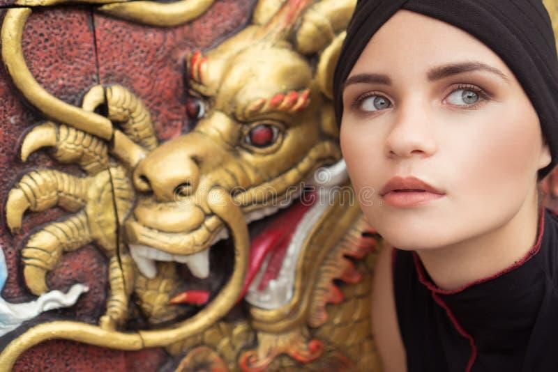 Forme el primer de la mujer joven con el sombrero negro sobre dragón de oro en la pared fotos de archivo libres de regalías