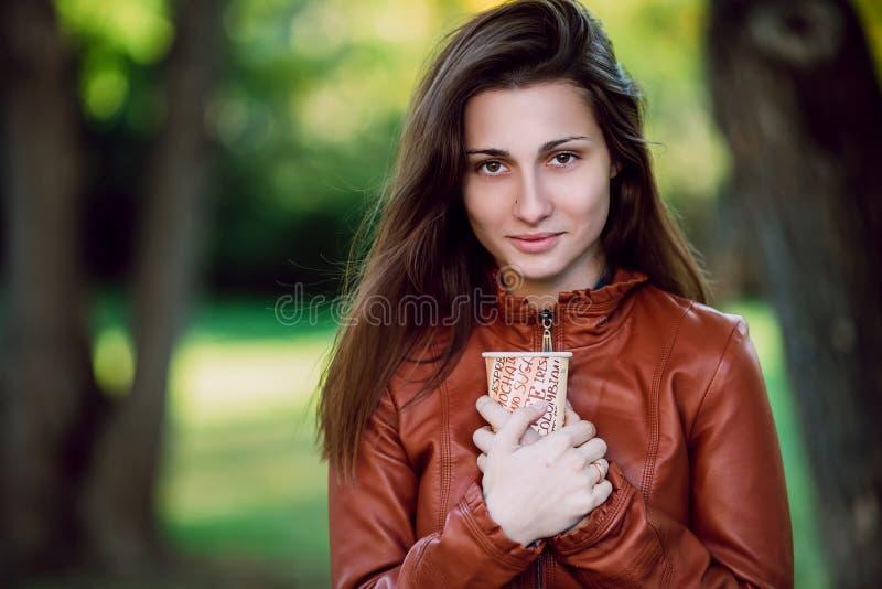 Forme el retrato al aire libre de la mujer larga magnífica del pelo en chaqueta de cuero marrón con la taza de coffe Muchacha de  foto de archivo