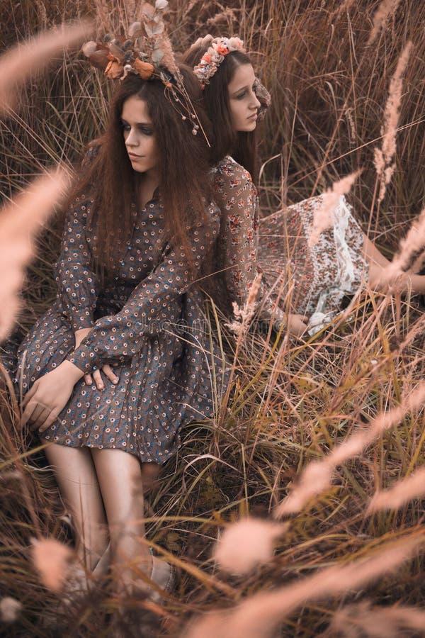 Forme el retrato de dos muchachas hermosas en la ropa diseñada boho que lleva del campo de la puesta del sol fotografía de archivo